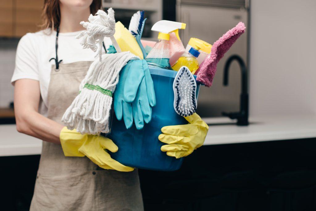 femme tenant un sceau et des produits ménagers